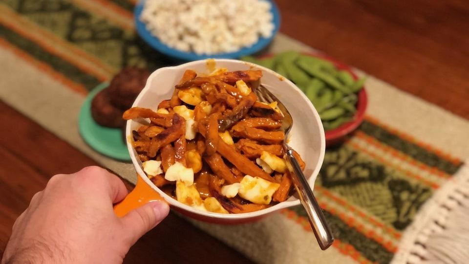 Une portion de poutine à base de patates douces, fromage en grains et sauce vindaloo.