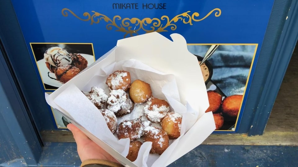 Une boîte de beignets congolais sur un fond bleu.