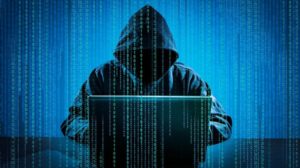 Une personne portant une veste avec un capuchon se trouve derrière un ordinateur.