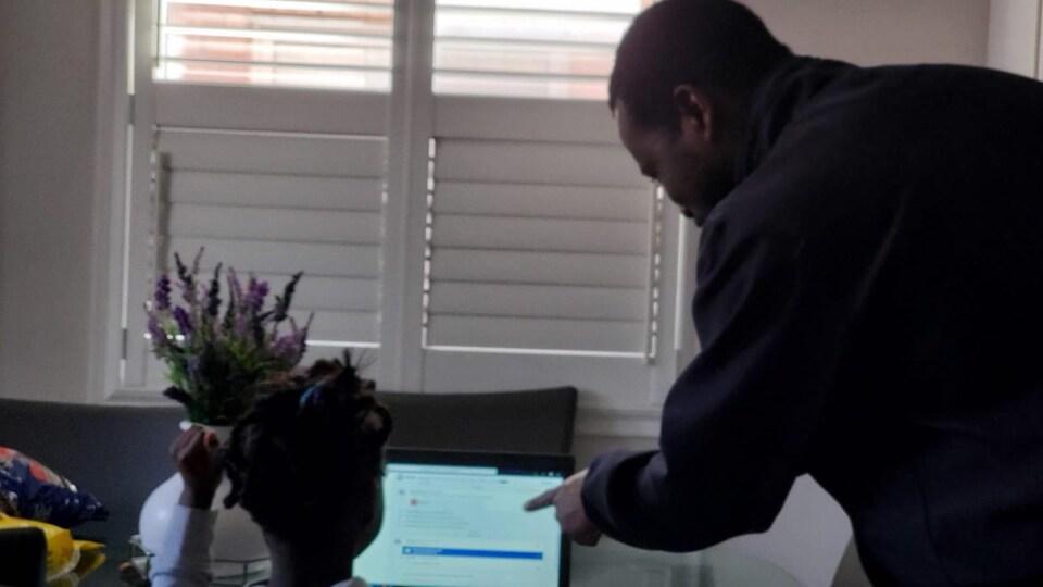 Hervé Atta aide  l'un de ses 3 enfants avec ses apprentissages scolaires.