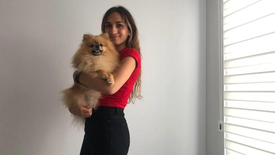 Lisa Lakreche tient son chien Lupi, un poméranien.
