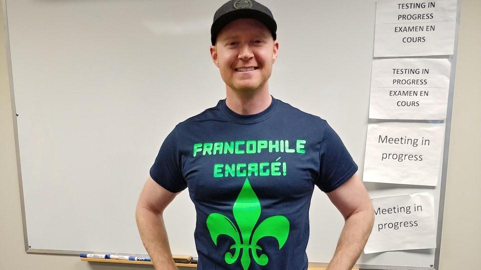 Un homme se tient debout arborant un t-shirt avec l'inscription «francophile engagé» sur le devant.