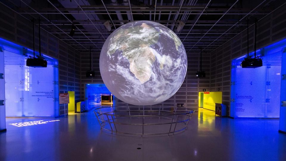 Un globe terrestre géant illuminé au milieu du Centre des science de l'Ontario.