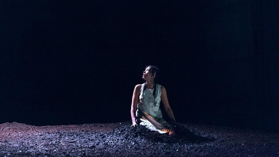 Une femme assise sur le sol.