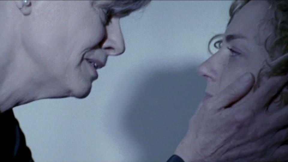 Une femme tient le visage d'une autre femme.