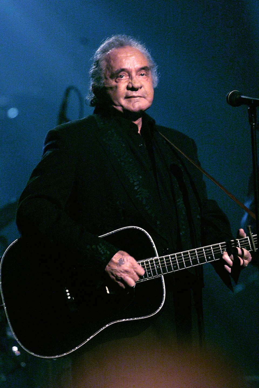 Johnny Cash, veilli, joue de la guitare en concert, en 1999.