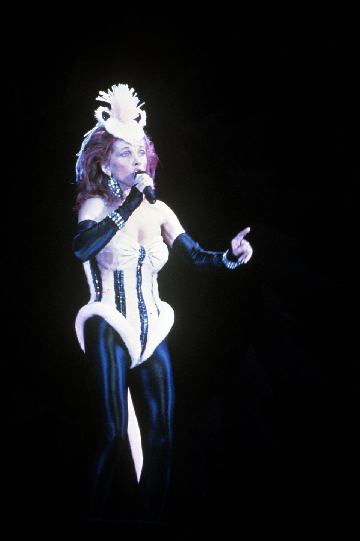 Une chanteuse habillée en costume et portant une coiffe sur la tête est sur scène.