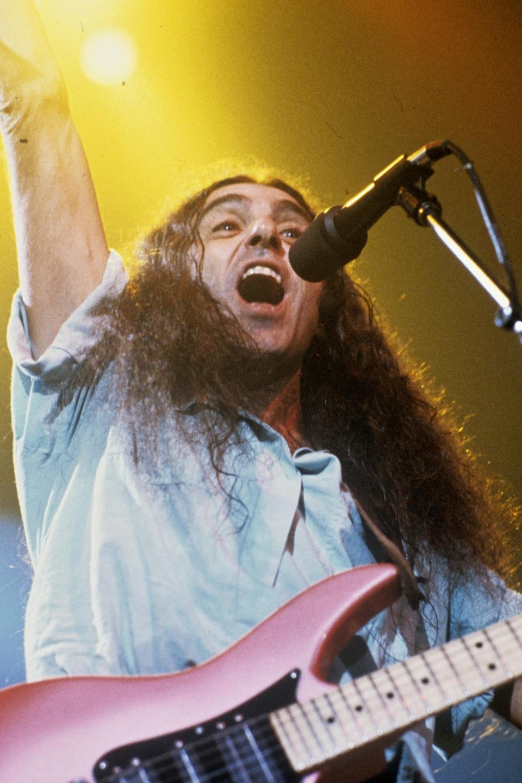 Gerry Boulet chante sur scène, une guitare électrique à l'épaule et le bras levé.