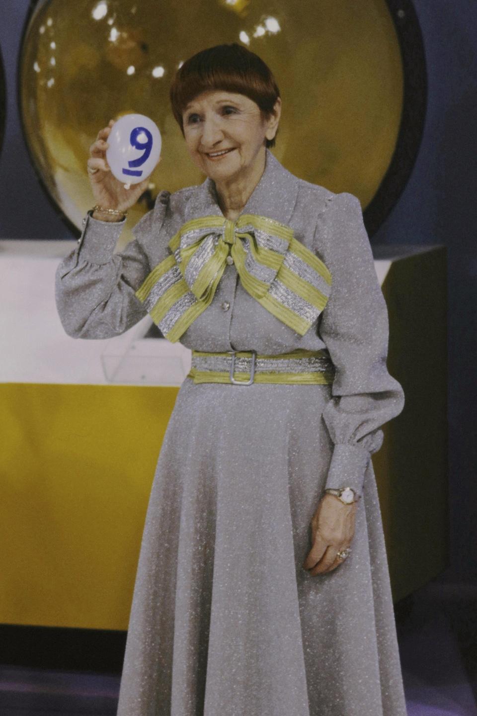 Rose Ouellet, vêtue d'une robe, tient une boule de loterie devant un boulier dans Bye bye 82.