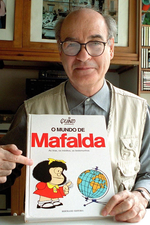 L'auteur de bande dessinée Quino tenant un livre de <i>Mafalda</i> en 1999.