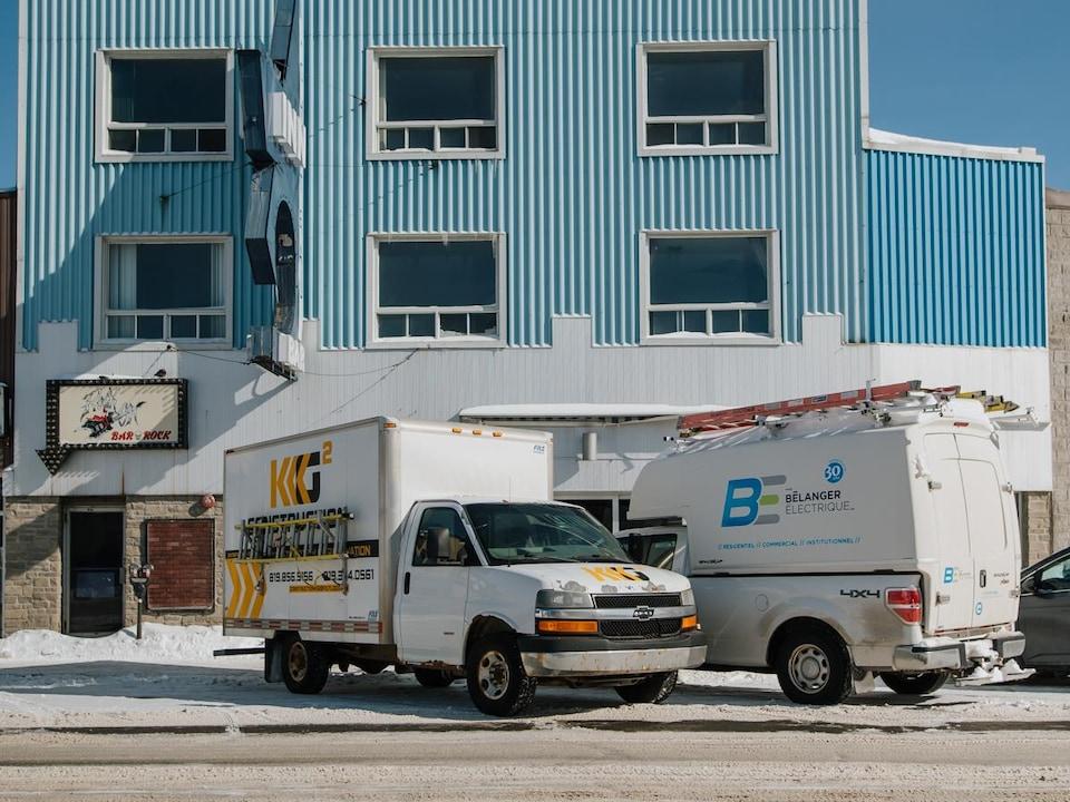 Un bâtiment de couleur bleu en hiver avec deux camions stationnés devant. Il s'agit du Chateau Inn de Val-d'Or.