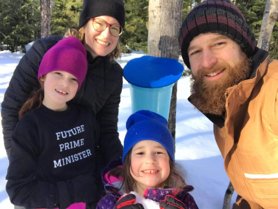 Famille de quatre devant une chaudière dans un érable.