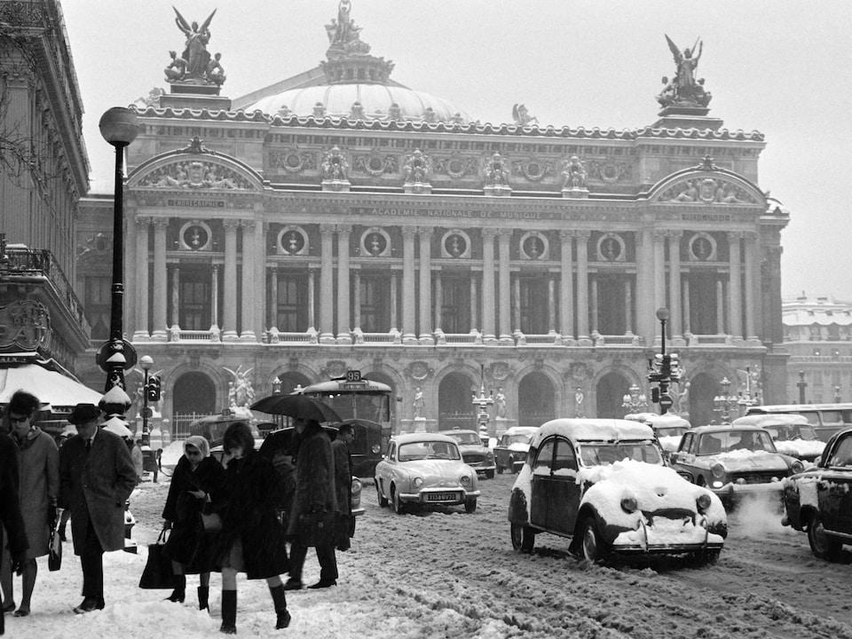 Photo en noir et blanc qui montre la place, des piétons et de nombreuses voiture empêtrées dans la neige.