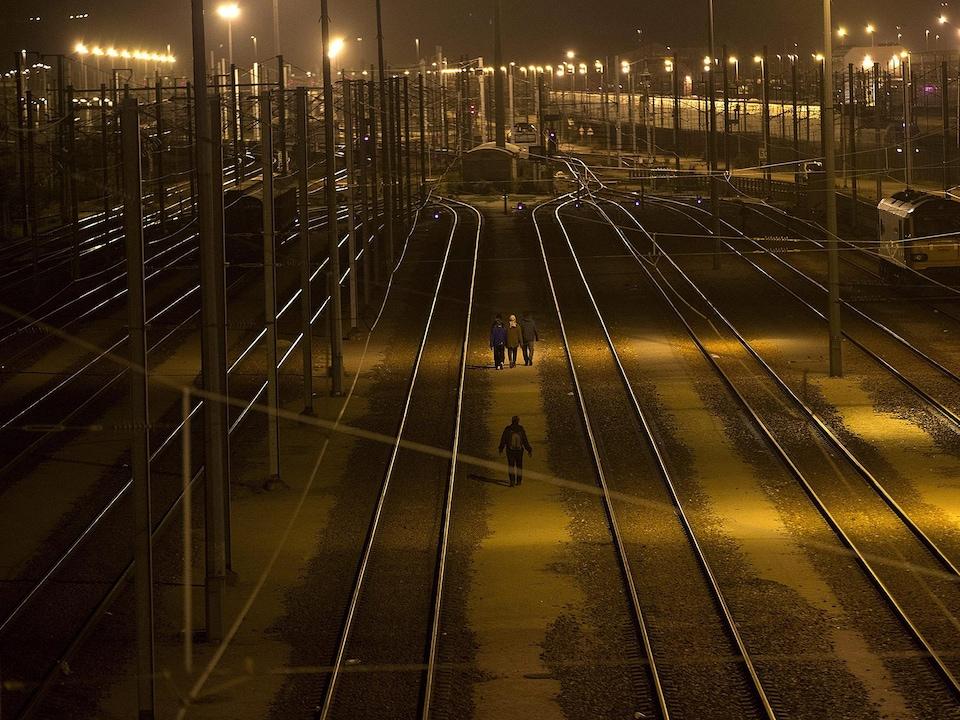 Quatre personnes marchent le soir près de rails de train.