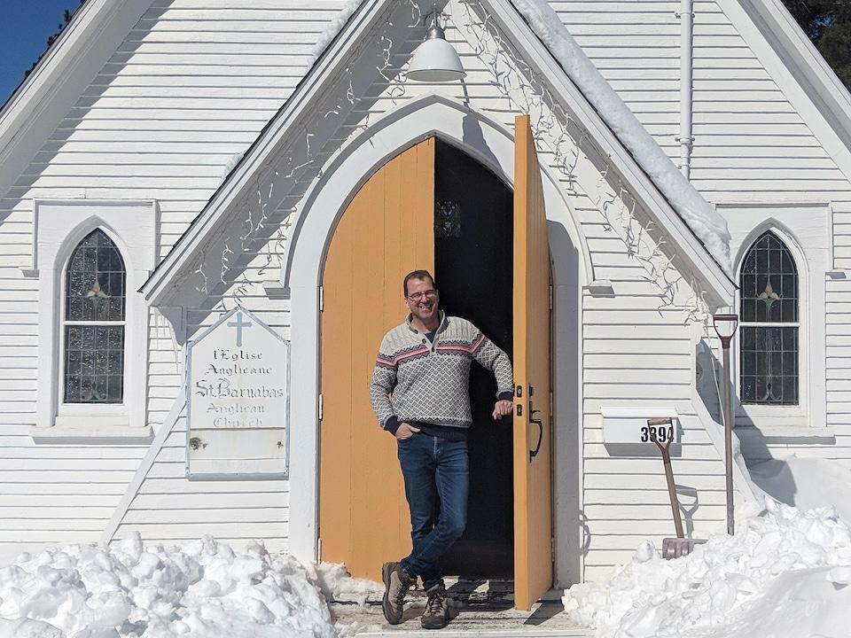 Un homme est devant une église anglicane en hiver, la main sur l'une des deux portes d'entrée qui est ouverte.