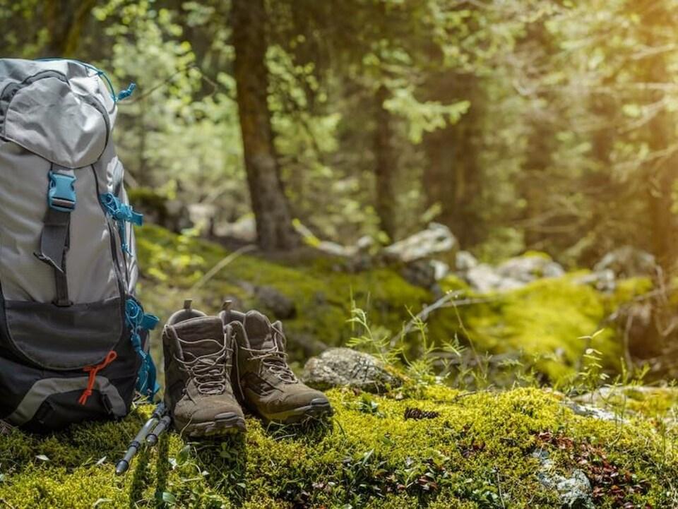 Des chaussures de marche et un sac à dos de randonneur dans une clairière en pleine forêt.