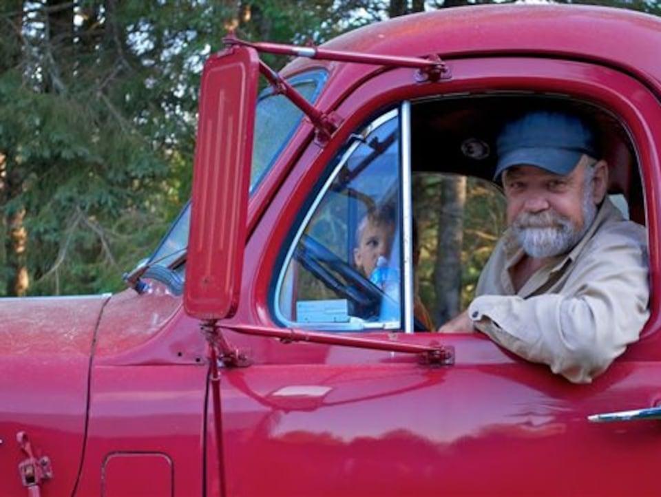 Serge Bouchard, souriant, au volant d'un camion rouge.