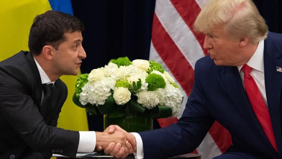 Deux hommes en complet se serrent la main devant un pot de fleurs et les drapeaux américain et ukrainien.