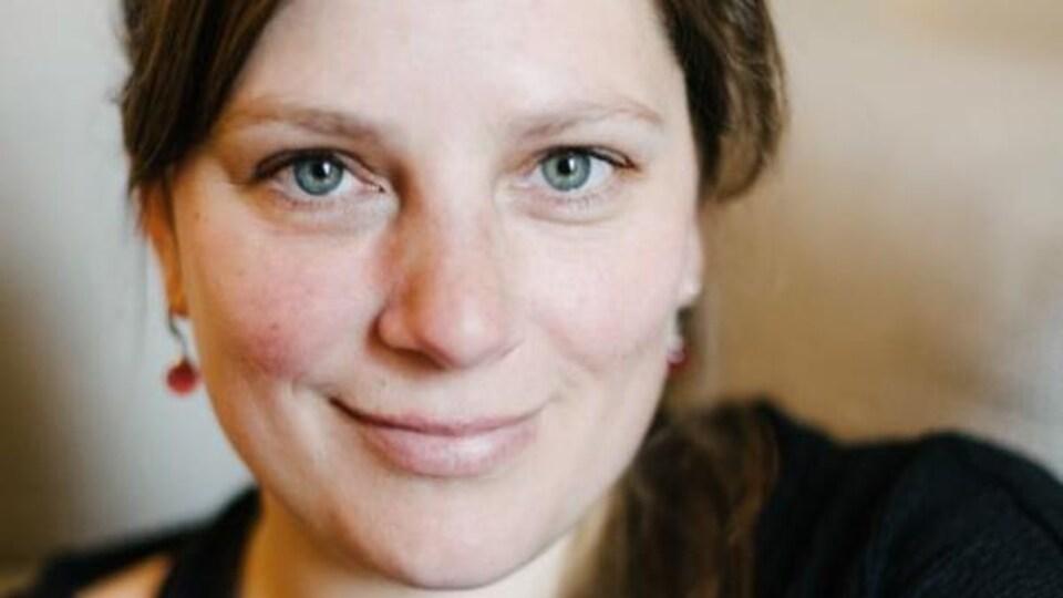 Portrait en couleur de l'autrice Annie-Claude Thériault, souriante, portant un chandail noir.