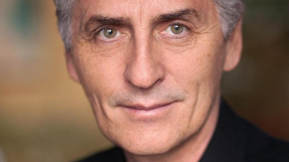 Portrait en couleur de l'auteur Larry Tremblay, en t-shirt et veston noir.