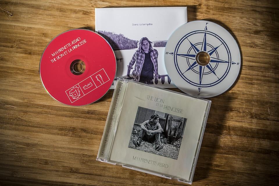 Deux albums de la discographie de Marie-Hélène Frenette-Assad, sur une table de bois.