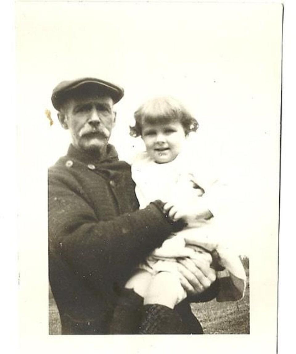 Photo en noir et blanc de François-Xavier qui porte dans ses bras sa petite fille. Il porte un béret.