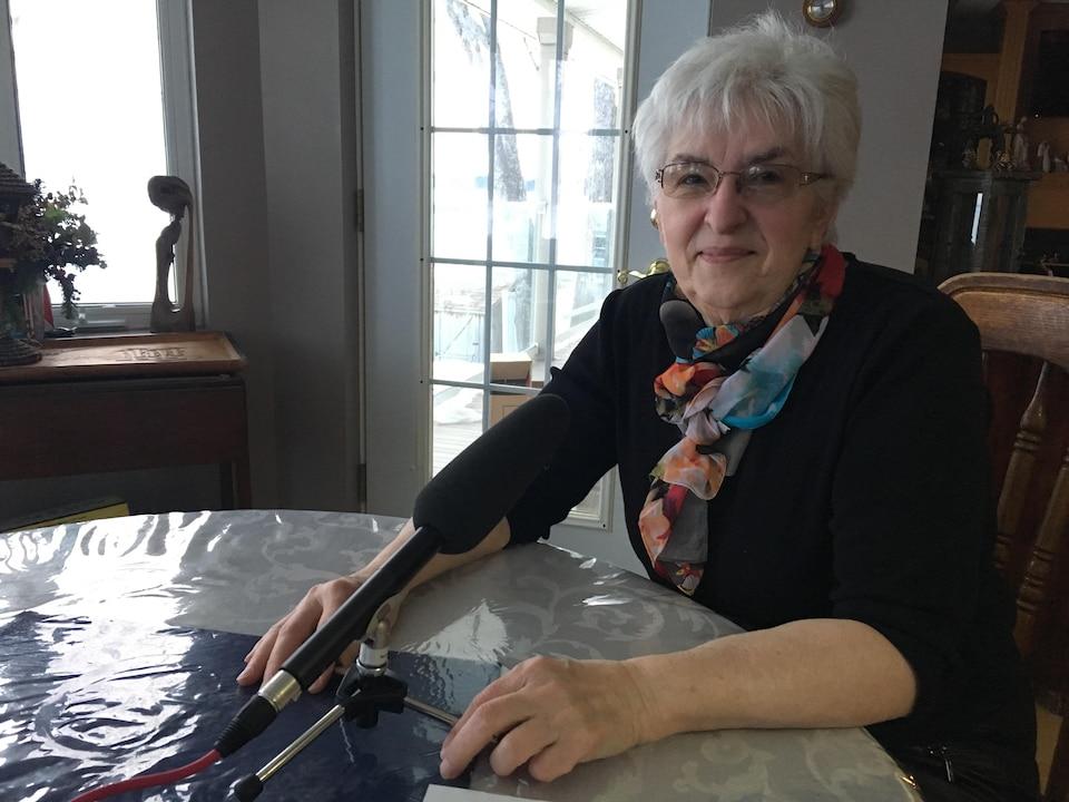 Raymonde, dans son salon, assise sur chaise de la salle à manger. Elle parle devant un microphone.