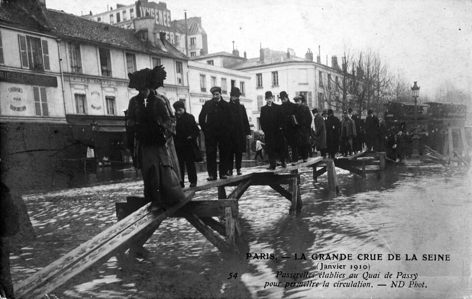 Photo en noir et blanc de piétons qui traversent la Seine sur un pont de fortune.