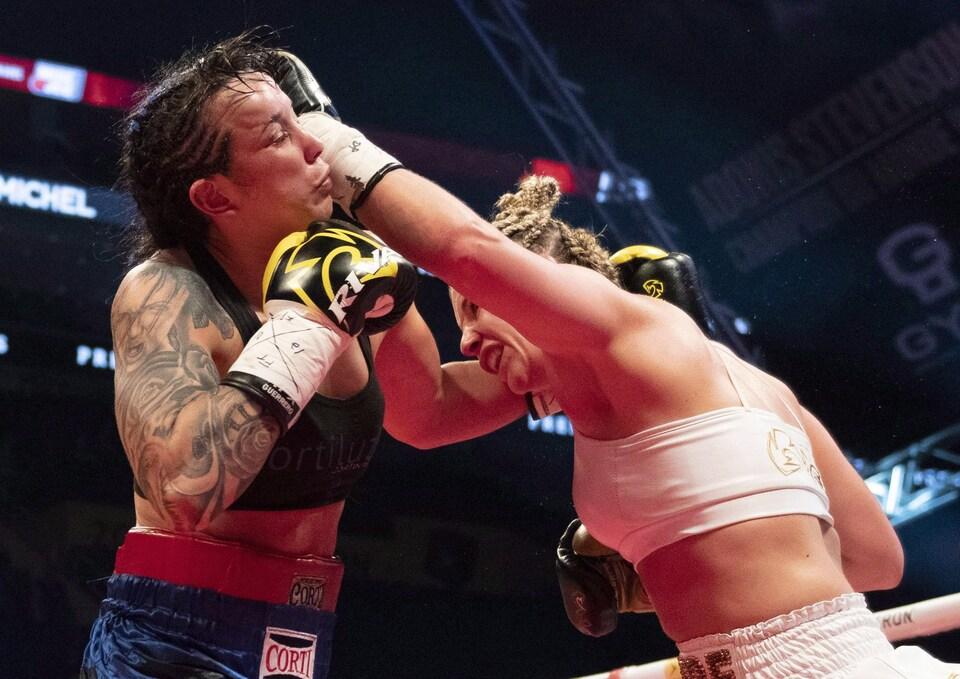 La boxeuse donne un coup au visage de son adversaire dans un ring.