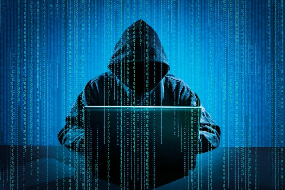 Une personne portant un capuchon travaille sur un ordinateur portable posé devant lui.