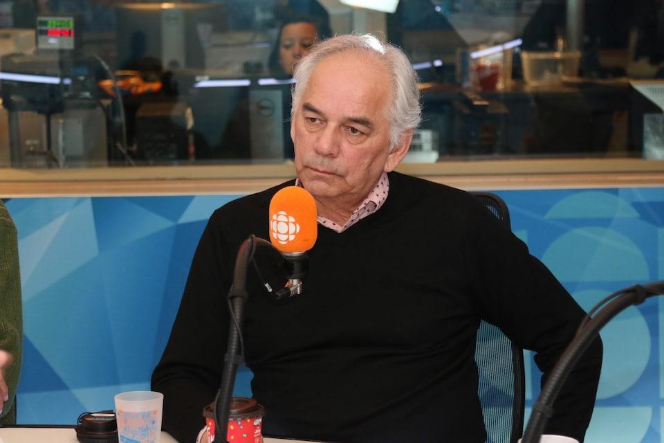 Ghislain Picard au micro du studio 17 de Radio-Canada, en train d'écouter une question de l'animateur