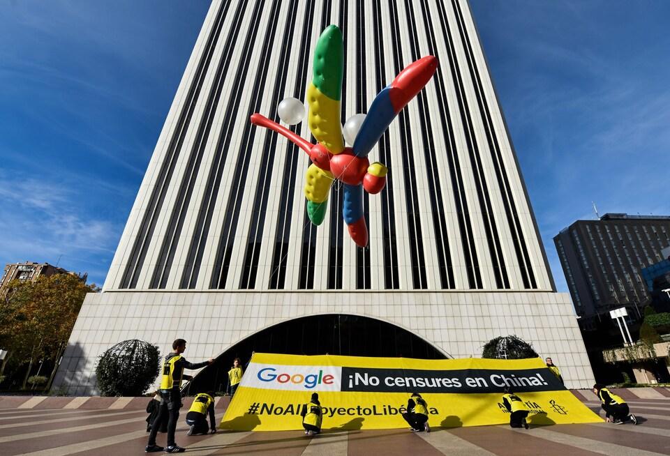 Des activistes d'Amnistie internationale tiennent un ballon géant en forme de libellule avec une bannière sur laquelle il est écrit : «Google, Pas de censure en Chine» lors d'une manifestation contre le projet de Google de lancer un moteur de recherche censuré en Chine.