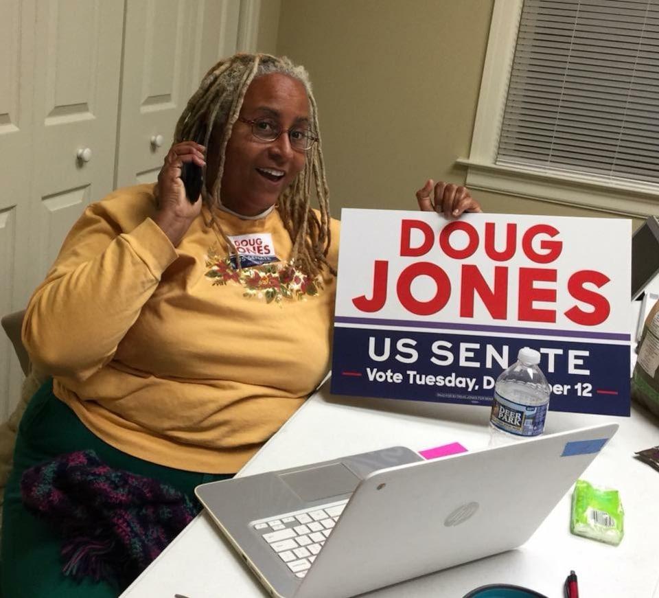 E-K Daufin, militante bénévole pour la campagne de Doug Jones, tient une pancarte électorale.