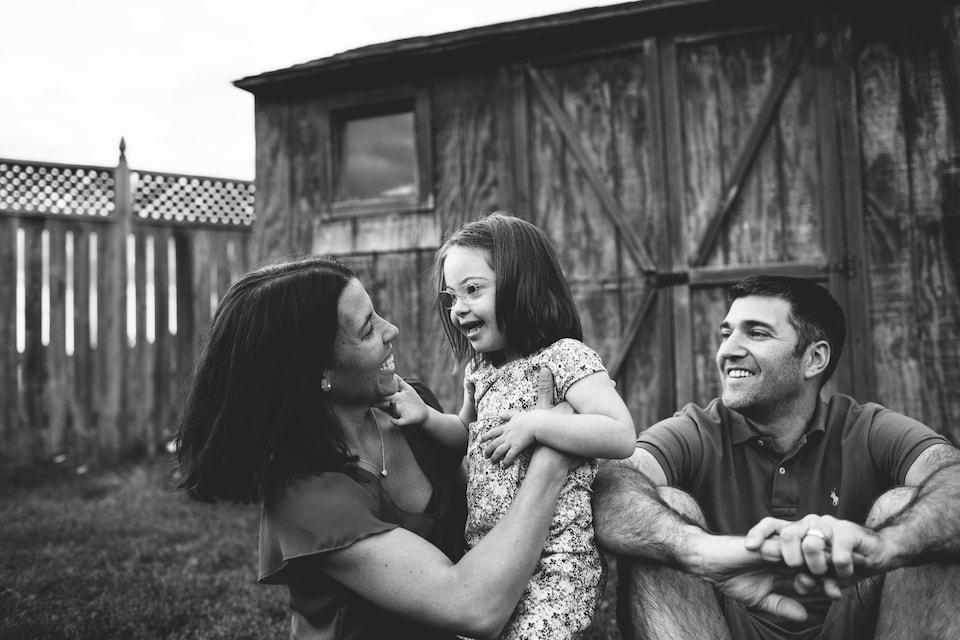 Élyse et ses parents dehors dans une cour devant une cabane en bois.