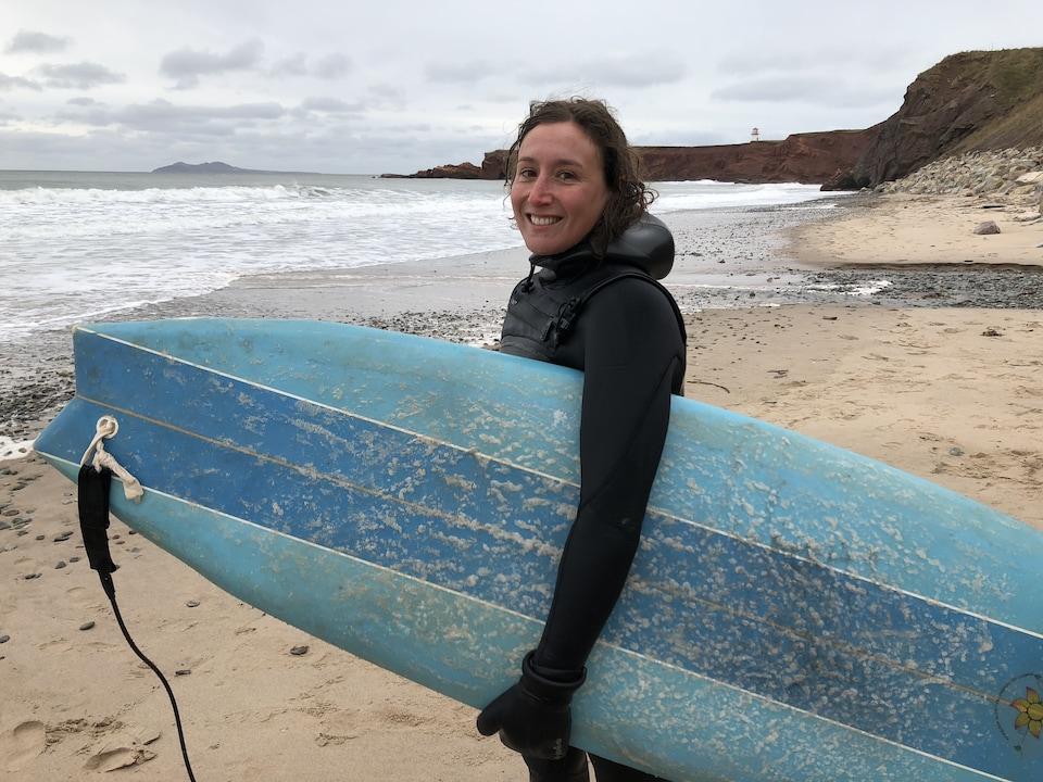 Fanny Boudreau pose avec son surf, en combinaison isothermique.