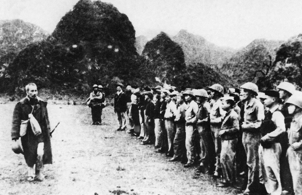 Photo en noir et blanc d'un homme devant des soldats.