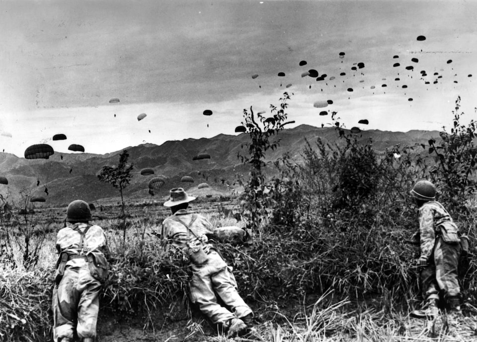 Photo en noir et blanc de trois soldats vus de dos qui regardent des parachutistes arriver.