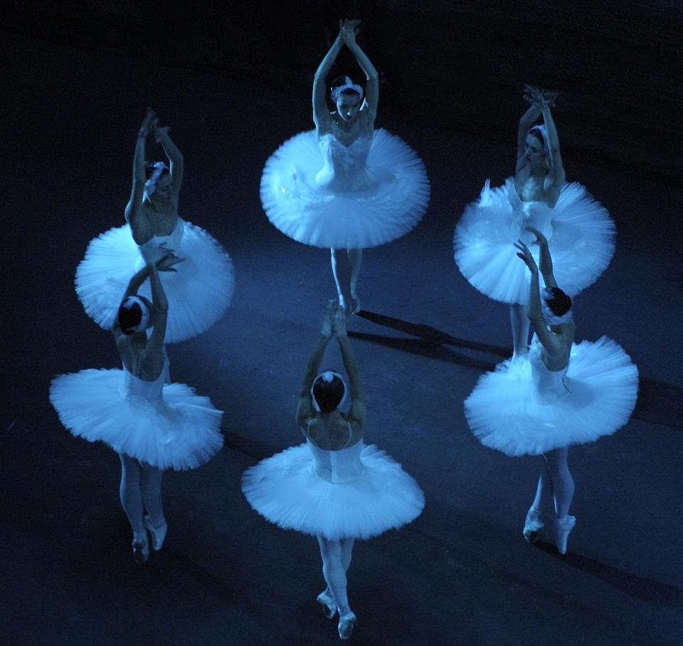 Sous un éclairage bleu, six ballerines costumées dansent avec les bras en l'air.