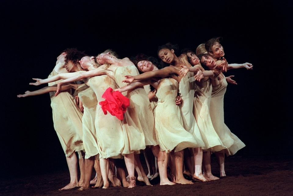 Des danseuses de la troupe de Pina Bausch tendent les bras.