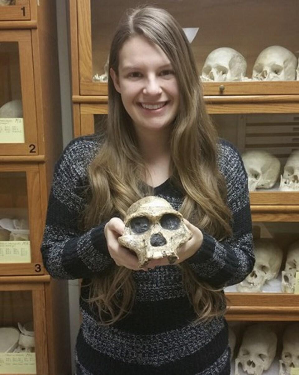 Jesseca Paquette, candidate à la maîtrise en paléoarchéologie à l'Université de Montréal qui tient un crâne dans ses mains.