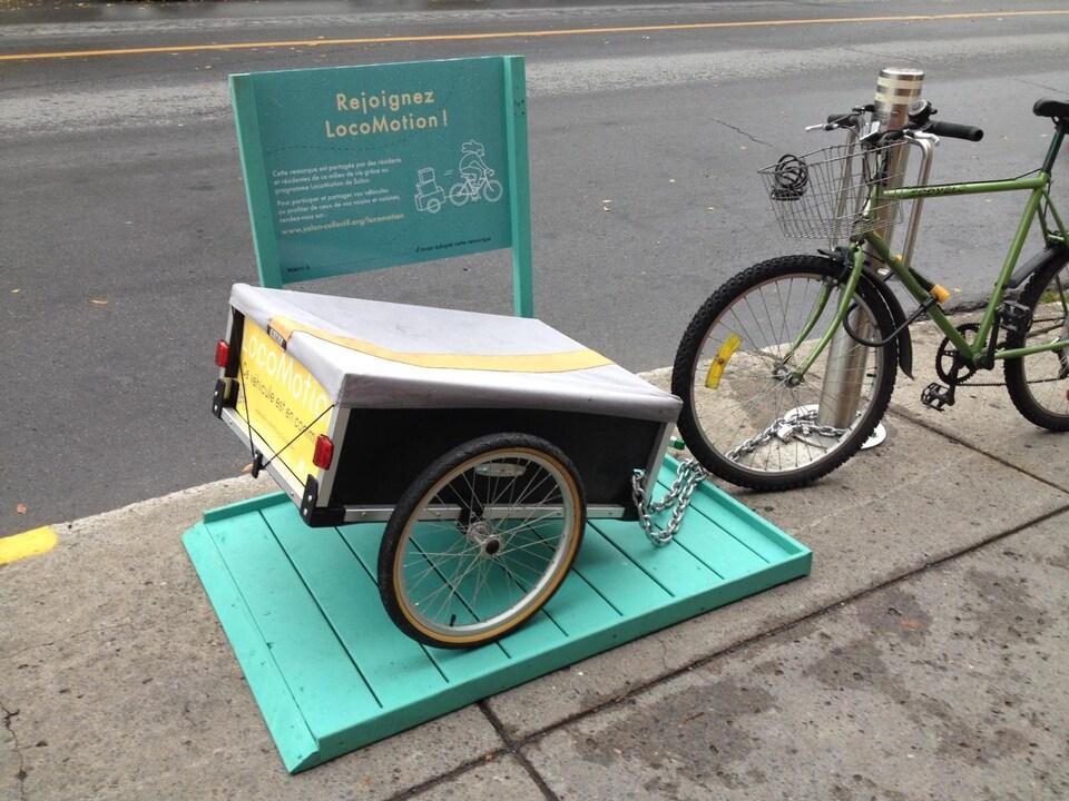 Une remorque à vélo, à deux roues, est attaché à un poteau sur un raque vert à côté d'une bicyclette.