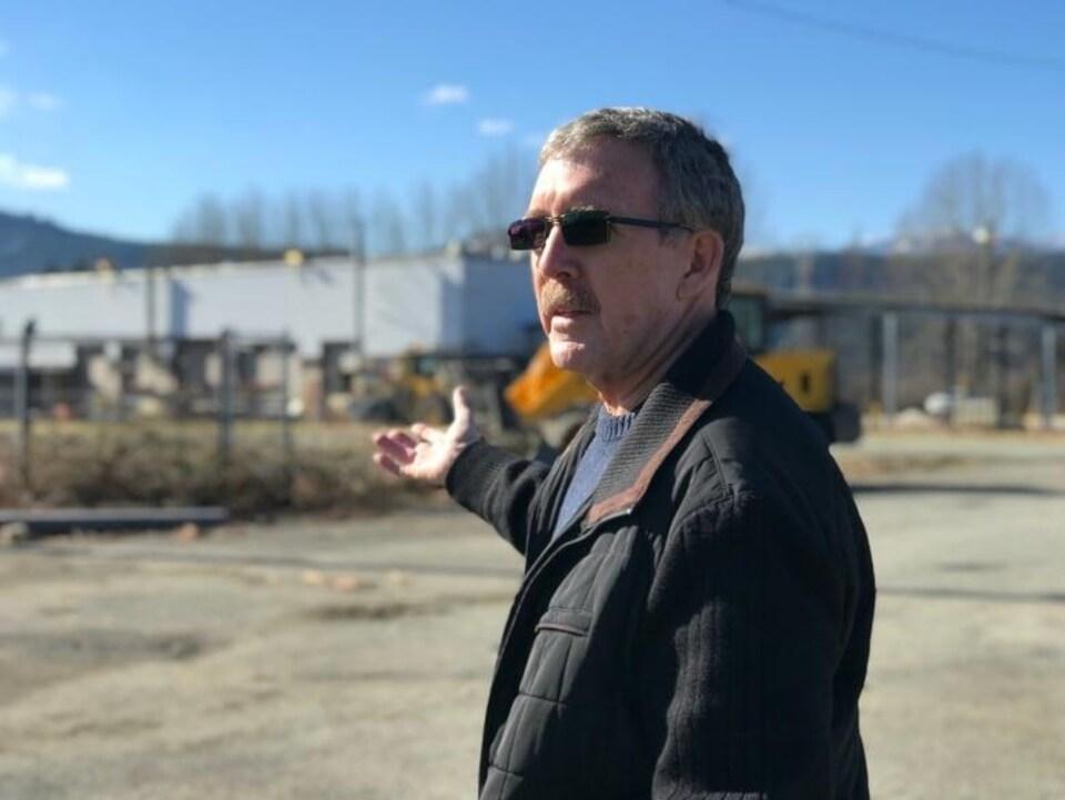 Un homme qui porte des lunettes noires montre une usine en pleine reconstruction.