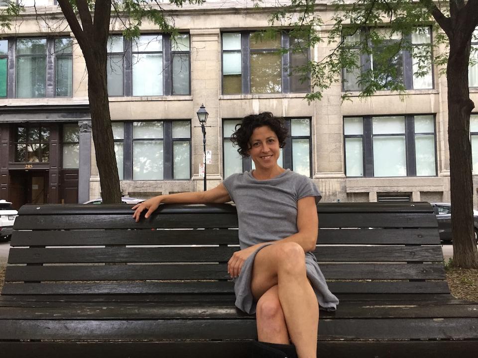 Hélène Dumais, assise sur un banc de parc.