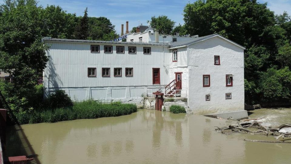 Un grand bâtiment blanc aux portes et fenêtres rouges près d'un cours d'eau.