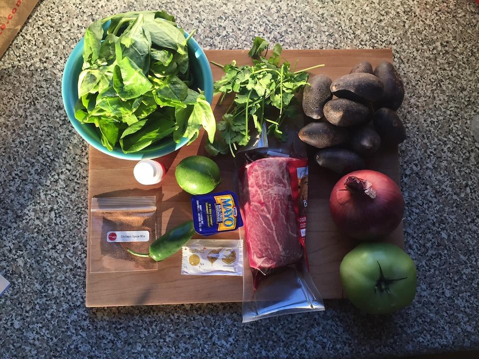 Des épinards, de la bavette, des pommes de terre, un oignon, une tomate verte, de la lime et des épices.