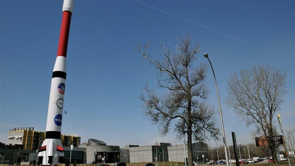 La fusée symbolique du Comsodôme devant celui-ci.