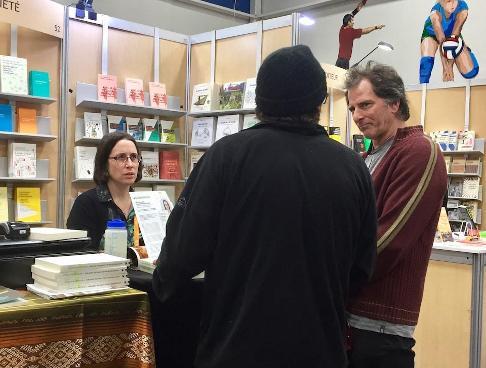 L'auteure Marie-Ève Maillé au Salon du livre de la Côte-Nord, discutant d'acceptabilité sociale avec le public, devant son kiosque de livres