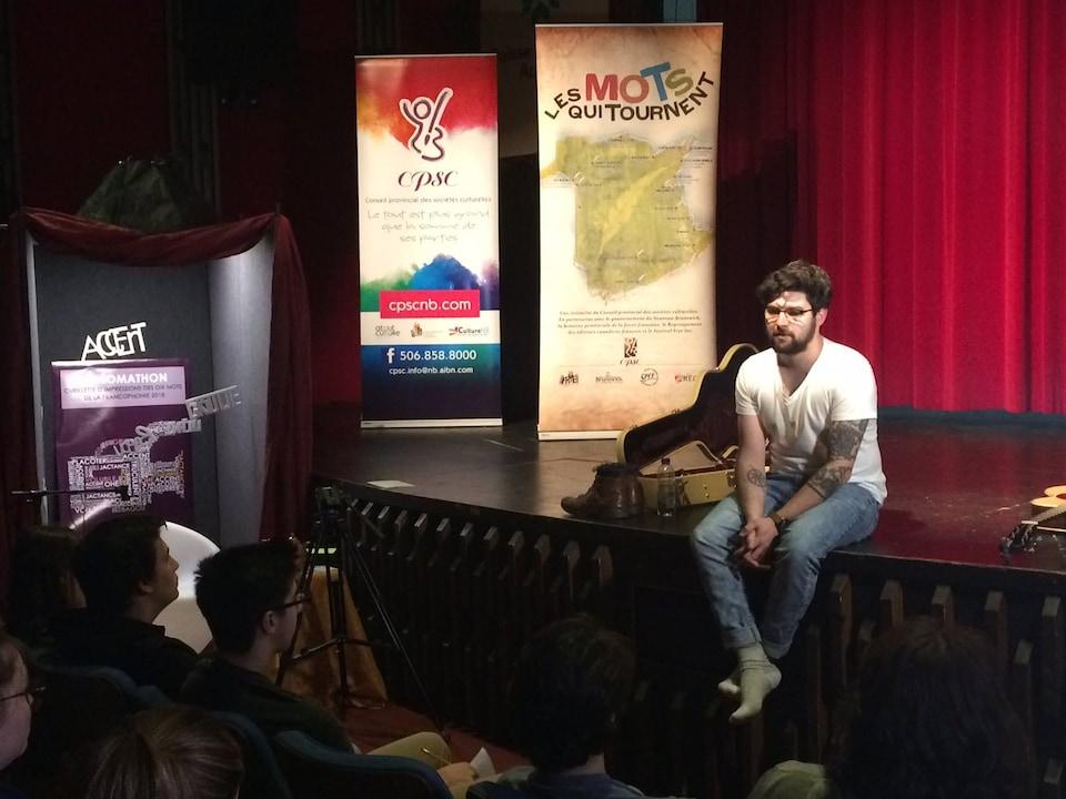 Sébastien Bérubé assis sur une scène.