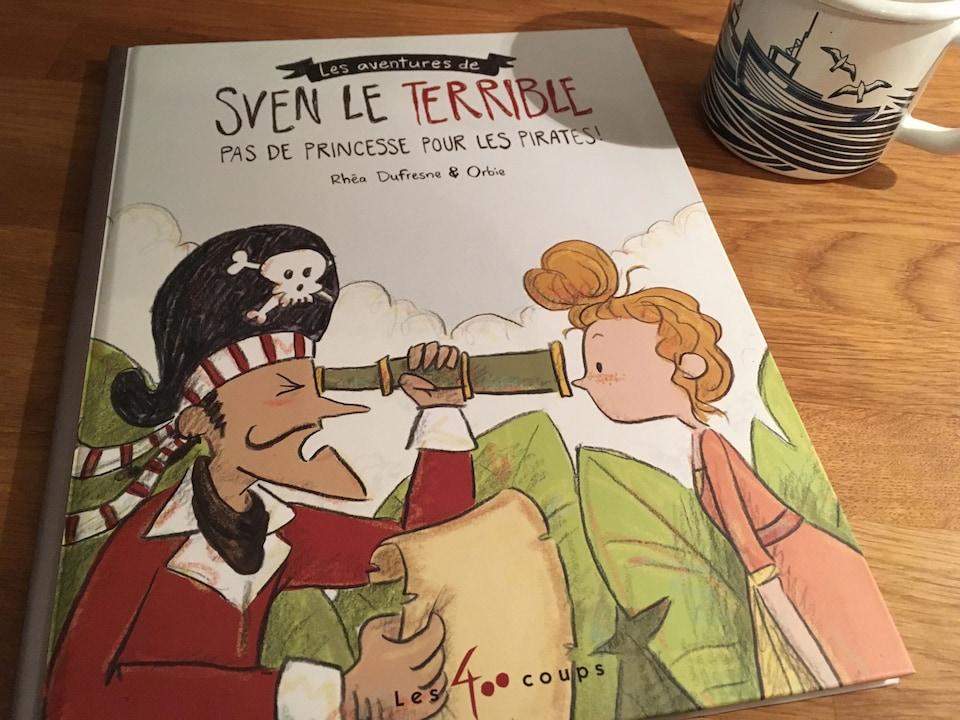 On voit la couverture d'un livre jeunesse. Un pirate regarde la figure d'une jeune fille à travers une longue vue.