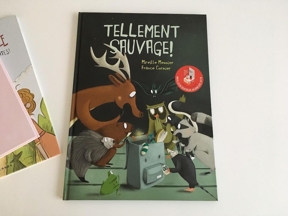 On voit la couverture d'un livre jeunesse. Il y a des animaux qui y sont illustrés dessus: un orignal, un raton laveur, un hibou, une souris.